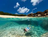 Split photo of young woman snorkeling in turquoise tropical water among huge granite boulders at The Baths beach area major tourist attraction on Virgin Gorda, British Virgin Islands, Caribbean poster