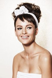 Beautiful brunette woman with retro hairdo and makeup. Luxury vogue style model posing in studio. Bridal makeup and wedding ideas concept.