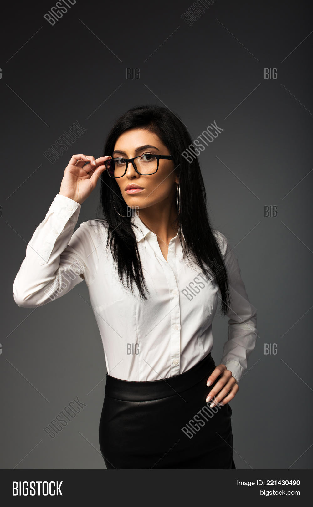 Sexy Brunette With Glasses In A White Blouse With A Black Leather Skirt