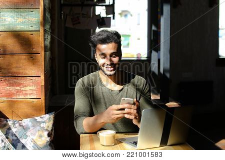 Two people sitting in caf by table near window. Modern laptop on table in front of man in dark sweater. Young woman talking with man. Couple laughing, bearded man and blond woman shake hands. Concept of comfortable caf for meeting.