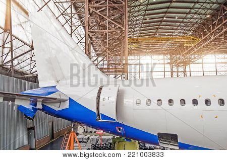 Passenger aircraft on maintenance, a view of the tail and the rear of the fuselage in airport hangar