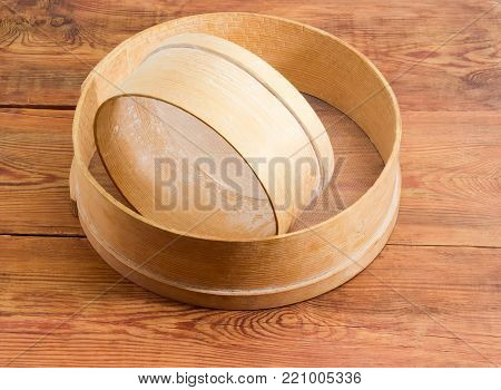 Two old round sieves different sizes with wooden frames and plastic mesh on an old rustic wooden surface