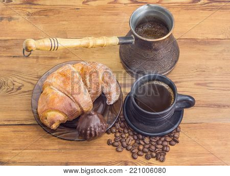 Freshly brewed black Turkish coffee in old copper coffee pot and black ceramic cup, croissant and chocolate truffle among of scattered roasted coffee beans on an old rustic wooden table
