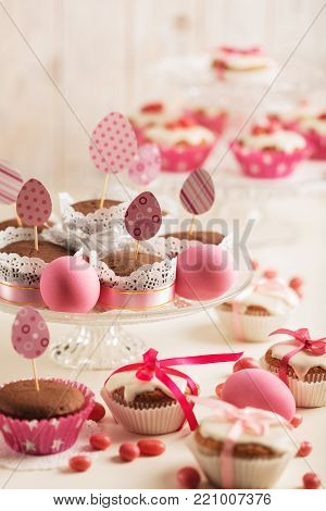 Easter eggs and Easter decor, paper eggs with a pink ribbon on a light wooden background. Selective focus.