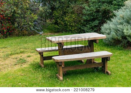 Wooden picnic table and two benches outdoors on green lawn