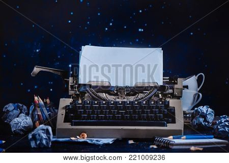 Modern typewriter with sheets of paper, empty coffee cups, pencils and notepads on a dark background. Editing and copywriting workplace. Creative writing concept.