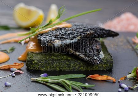 Grouper's grilled fillet on a spinach bed. Fish on the black slate, shale board. Lemon pieces, sauce and rosemary. Piece of fish on wooden table, close up