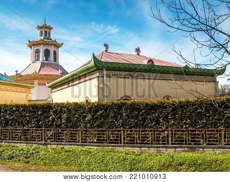 A Chinese-style pavilion with a dragon on the roof and a green fence made of thuya in the Alexander Park in Pushkin in St. Petersburg in the early spring in early May on a clear, sunny day