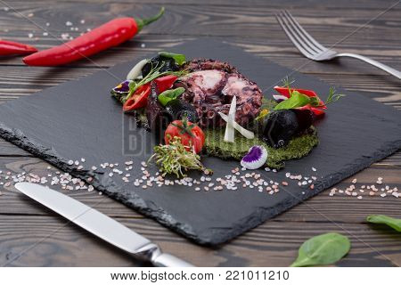 grilled octopus with vegetables on black shale board. Octopus with chili and spinach. Tasty seafood on slate on wooden table. Top view