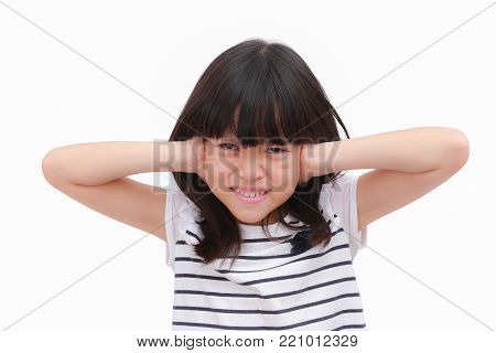 Asian kid girl express stress face and raise her hand close her ears. Put on black striped white T-shirt. isolate on white background, Portrait image.