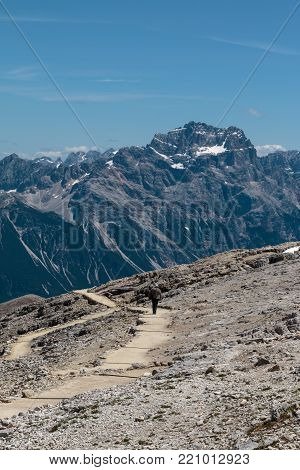 Man with Hat Walking in Stone Path among Barren Mountains in Italian Dolomites Alps in Summer Time.