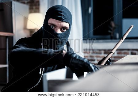 Burglar. Concentrated dark-eyed masked burglar wearing a uniform and holding a folder while looking for something in the table