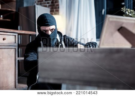 Thief. Serious dark-eyed masked thief wearing a black uniform and holding a folder while stealing important papers from the table