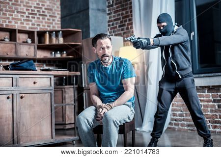 Fear. Frightened trembling bearded man sitting with his hands tied while a criminal holding a gun and wearing a mask and uniform