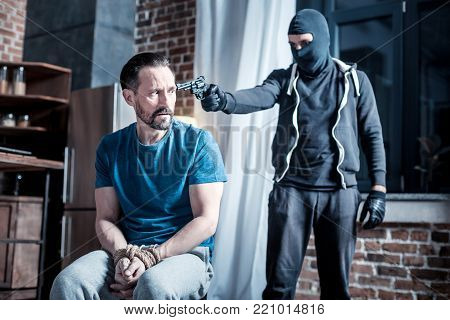 Victim. Scared trembling bearded man sitting with his hands tied while a criminal holding a pistol to his head and wearing a mask and uniform