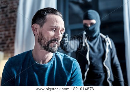 Terror. Terrified trembling bearded man sitting while a masked criminal standing behind him and holding a pistol to his head