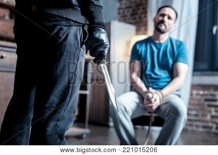 Crime. Terrified trembling bearded man sitting with his hands tied while a masked criminal standing in front of him and holding a knife