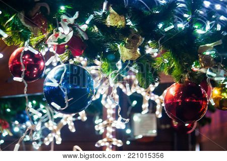 Fir-tree branches adorned with balls and lights. New Year and Christmas balls and lights in the evening