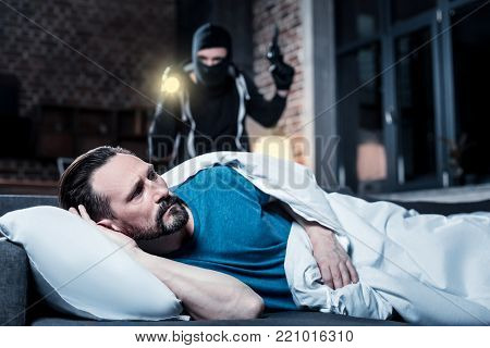 Who is here. Alarmed disturbed bearded man waking up and hearing someone being in his house and a masked criminal with a torch and gun standing behind him