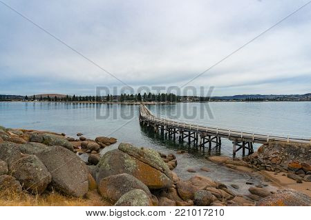 Long bridge, jetty to the island with rocks on the foreground. Victor Harbor, South Australia
