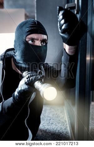 Thief. Dark-eyed professional masked burglar opening a window and holding a torch while breaking into the house and wearing black gloves
