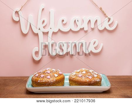 two festive cakes with hearts under welcome home words