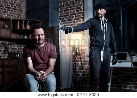 Killer. Frightened panic bearded man sitting with his hands tied and eyes closed while a criminal standing near him and holding a gun at his head
