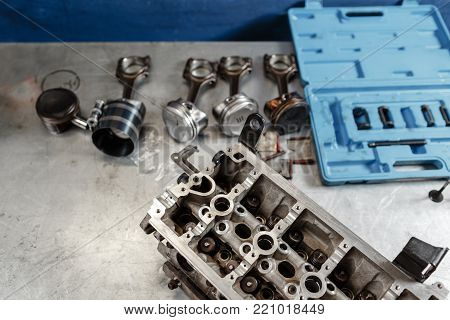 Disassemble engine block vehicle. Motor capital repair. Sixteen valve and four cylinder. Car service concept. The job of a mechanic. Old and new pistons. Top view.
