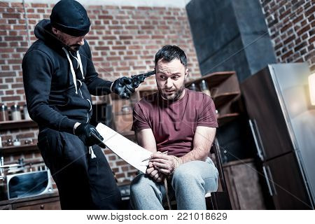 Signing a contract. Panic intimidated bearded man sitting with his hands tied while a killer standing near him and holding a gun and making the man sign a contract