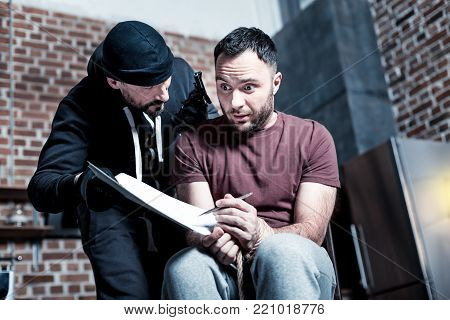 Contract. Panic frightened bearded man sitting with his hands tied while a killer standing near him and holding a gun and making the man sign a contract