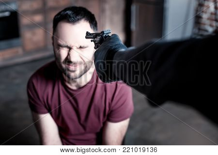 Death. Panic alarmed bearded man sitting with his eyes closed while a burglar standing near him and holding a gun at his head