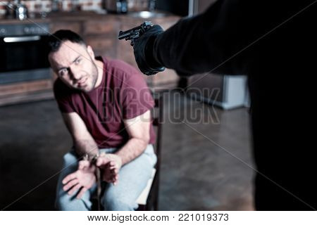 Give me chance. Shocked frightened bearded man sitting with his hands tied while a killer standing near him and holding a gun