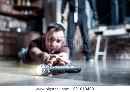 Lying on floor. Scared panic bearded man lying on the floor and having his hands tied and reaching for a torch while a killer standing behind him