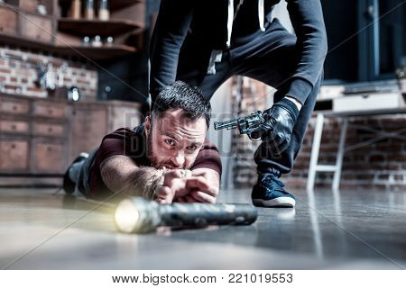 Reaching for torch. Scared frightened bearded man lying on the floor and having his hands tied and reaching for a torch while a killer standing behind him and holding a gun at his head