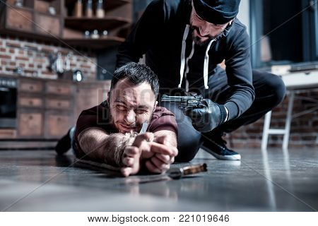 Reaching for knife. Scared frightened bearded man lying on the floor and having his hands tied and reaching for a knife while a killer sitting near him and holding a gun at his head
