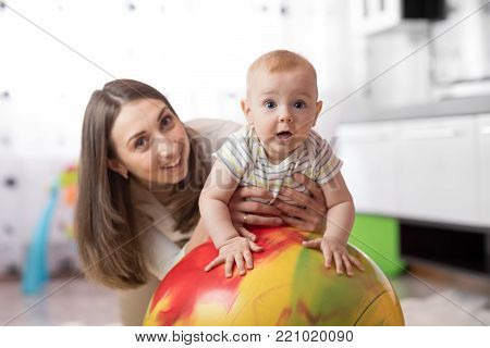 Mother doing exercises on a fit ball with baby.