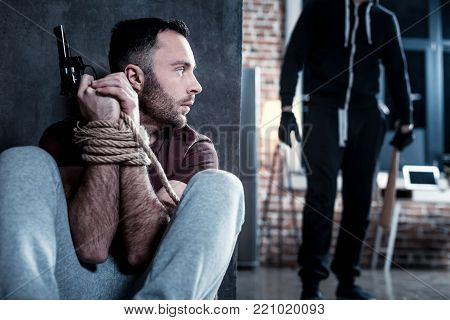 Hiding from killer. Frightened shocked bearded young man holding a gun and sitting with his hands tied while hiding from a killer holding a stick