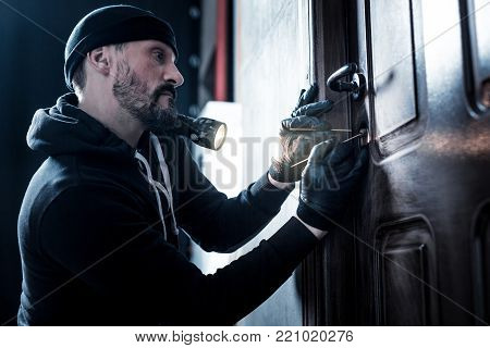 Unlocking. Serious professional bearded robber holding a torch and wearing gloves and unlocking the door poster