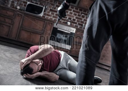 Fright. Scared dark-eyed bearded man lying on the floor in the kitchen and covering his head with hands and a killer holding a pistol at his head