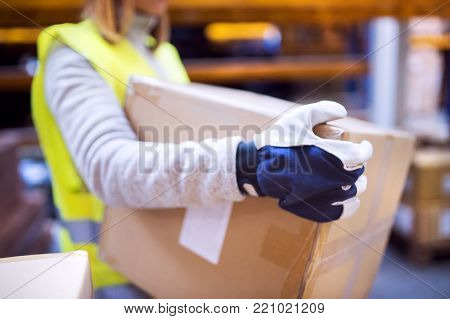 Unrecognizable female warehouse worker loading up a pallet truck with boxes.