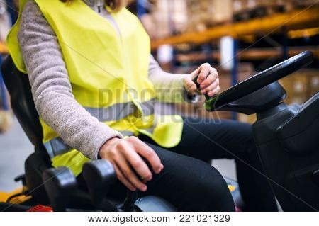 Unrecognizable young woman warehouse worker with forklift.
