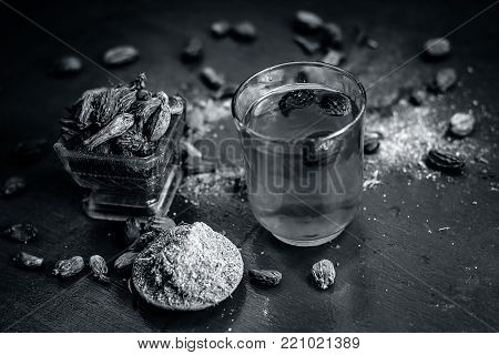 Close Up Of Water Of Black Cardamom With Its Powder And Raw Whole Black Cardamom.