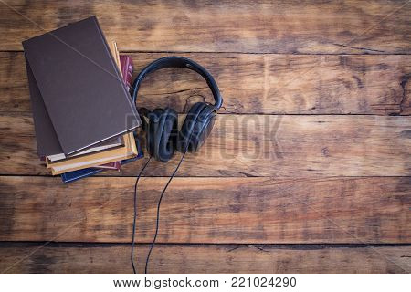Headphones and a pile of Books on the Wooden Table. Audiobook Concept.