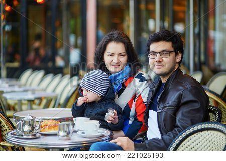 Happy Family Of Three In Parisian Outdoor Cafe