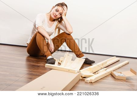 Worried helpless woman assembling wooden furniture. DIY enthusiast. Young girl doing home improvement.
