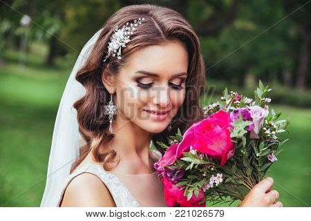 Beautiful bride outdoors in a park . Bride holding a bouquet of flowers in her hand,