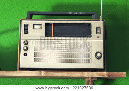 Old radio in vintage color. Radio standing on the shelf.