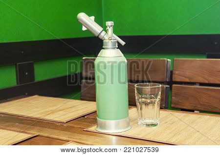Green vintage soda syphon, standing on a wooden table.