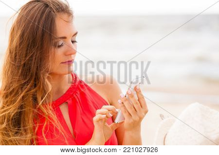 Contact and connection. Summer time. Young pretty long haired woman with smartphone texting and sending sms messages.
