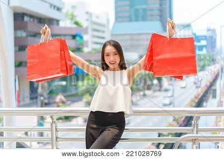 Beautiful young woman show shopping bags over the path way to the shopping mall. department store summer sale and fashion at center complex bangkok.